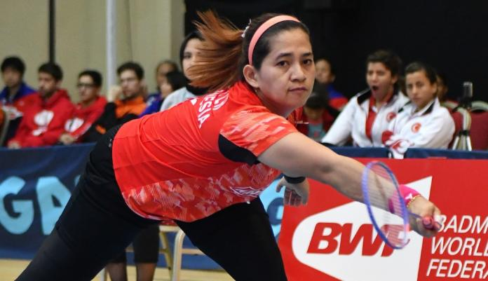 Para-badminton player bends down to hit a forehand
