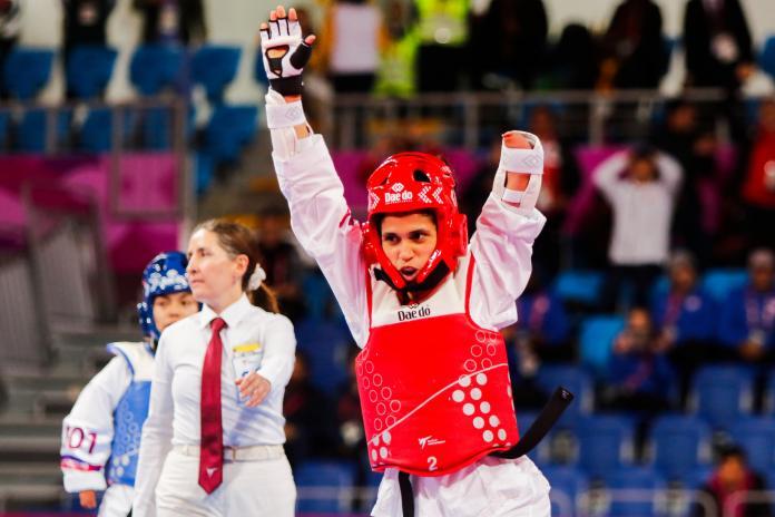 a para taekwondo athlete raises her arms to celebrate