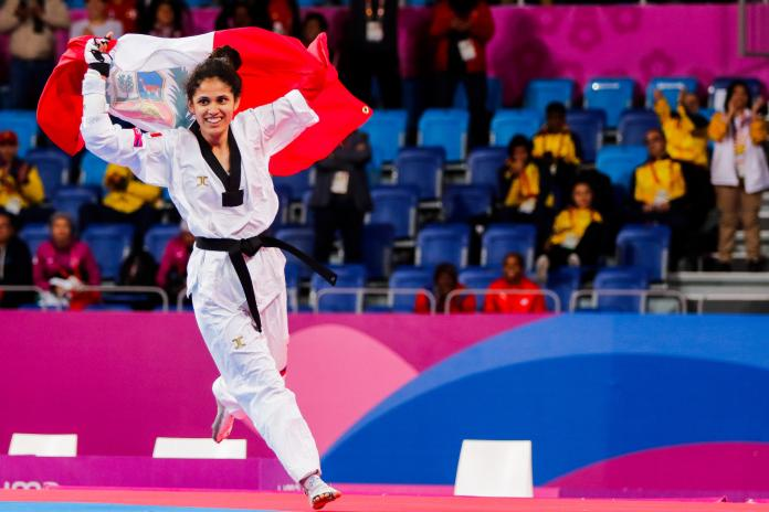 una atleta de Para taekwondo que lleva la bandera de Perú