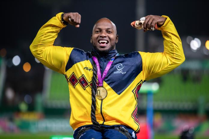 Un atleta masculino en silla de ruedas con una medalla de oro alrededor de su cuello levanta las manos