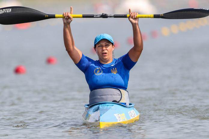 A woman in a kayak lifts a paddle above her head