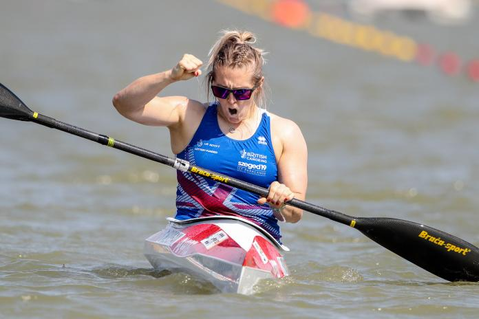 Woman in kayak clenches fist to celebrate