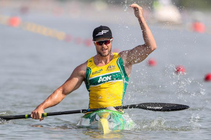 Man in kayak splashes water to celebrate victory