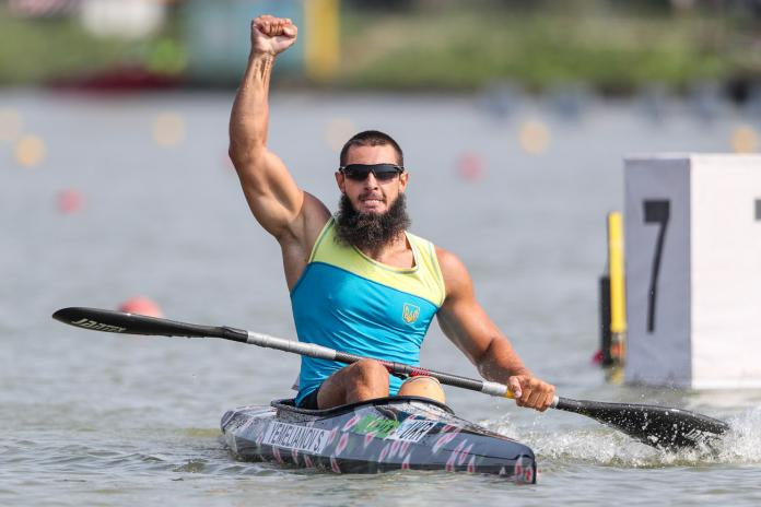 Man in kayak raises fist in the air to celebrate