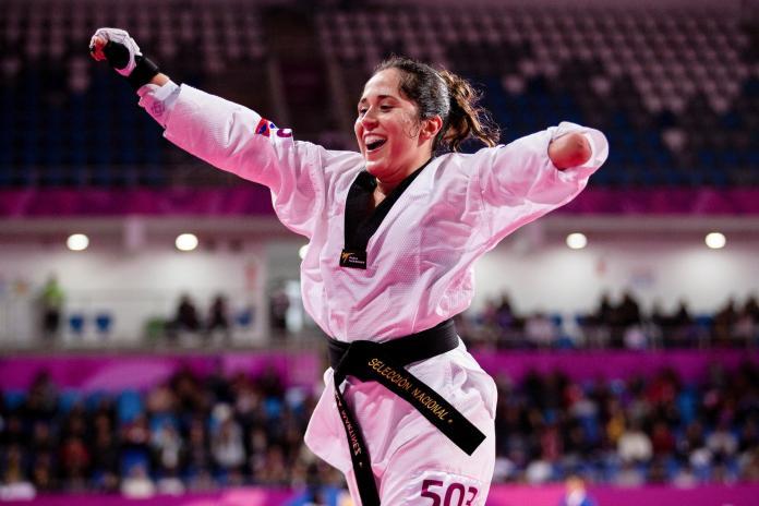 Una atleta de Para taekwondo levanta los brazos en celebración