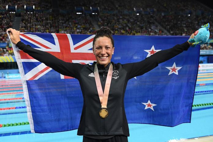 Nuotatore para femminile che tiene la bandiera della Nuova Zelanda