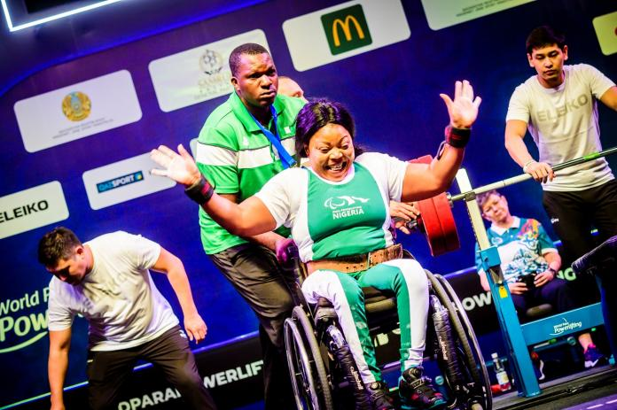 A woman in a wheelchair celebrating with a man standing behind her during a para powerlifting competition