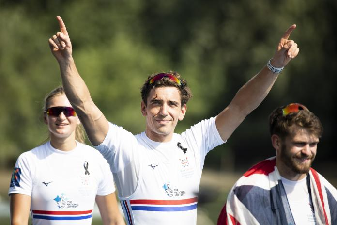 The male British rower smiles with both arms raised