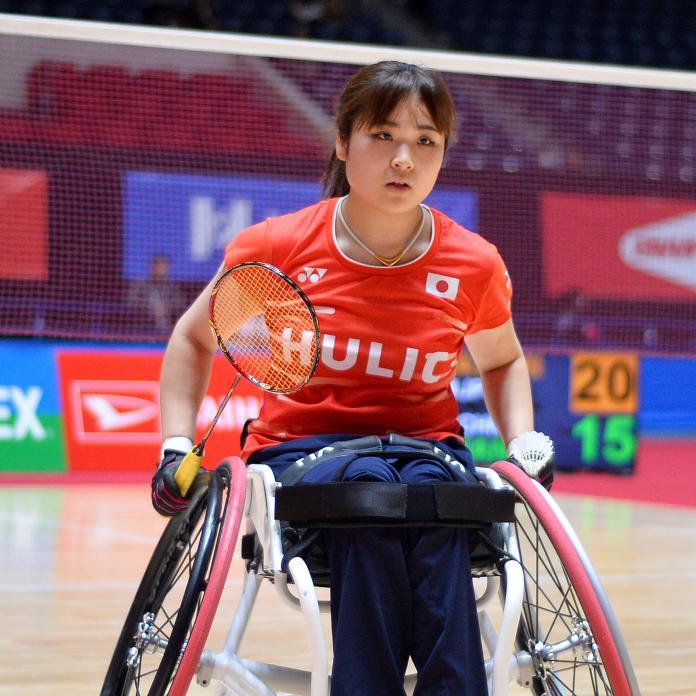 Japanese female athlete in wheelchair holds racket and shuttle