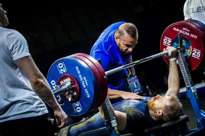 A man on a bench press prepares to lift a barbell with three men standing around him