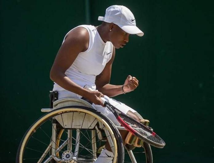 Den svarte kvinnelige rullestoltennisspilleren feirer et poeng
