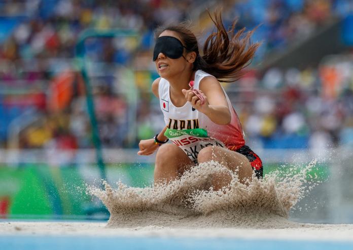 Un long saut japonais qui obstrue la vue, tombant sur le sable après son saut