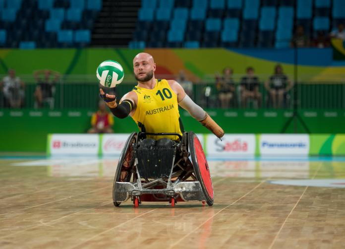 Male wheelchair rugby player tries to grab the ball