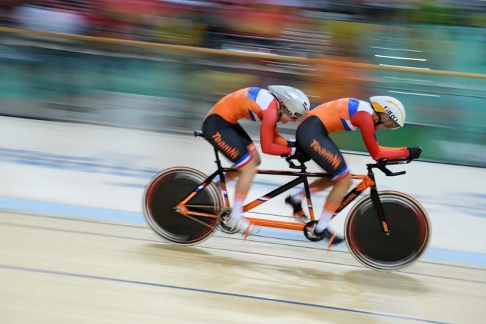 Dutch tandem track cyclists riding in a velodrome