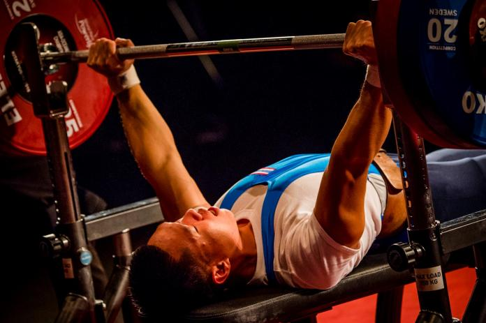A man on a bench press lifting a barbell in a Para powerlifting competition