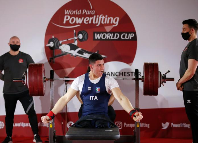 Legless man on bench press celebrating celebration watched by two other men standing in para powerlifting competition