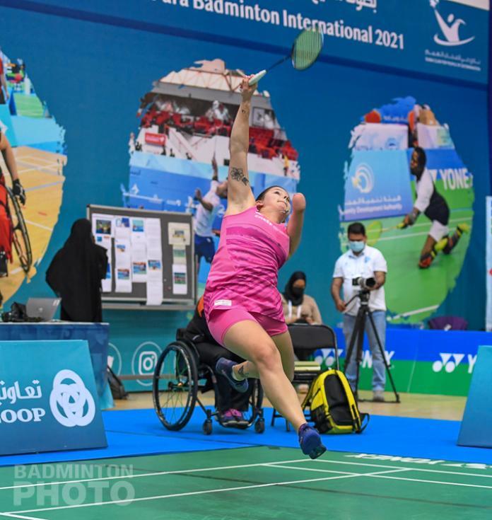 Een badmintonspeler met een zwakke arm springt terug naar de shuttle