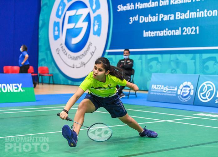 Een jonge badmintonspeler met zwakte in haar linkerarm snelt naar de shuttle