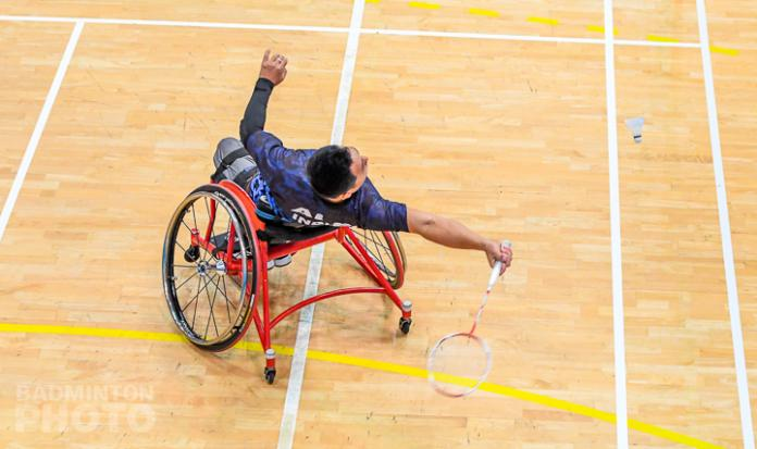 Een man in een rolstoel reikt naar achteren om met een shuttle terug te keren