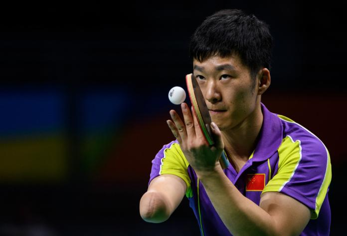 Male chinese table tennis with missing right arm serves the ball