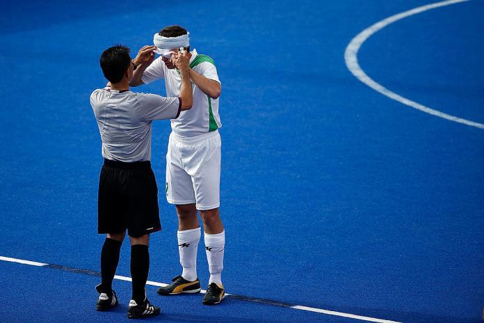 O árbitro verifica as viseiras do jogador de futebol cego