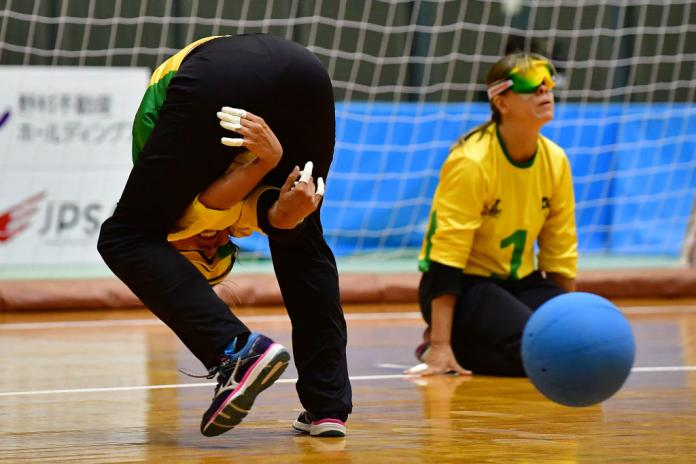The woman throws goalball between the legs