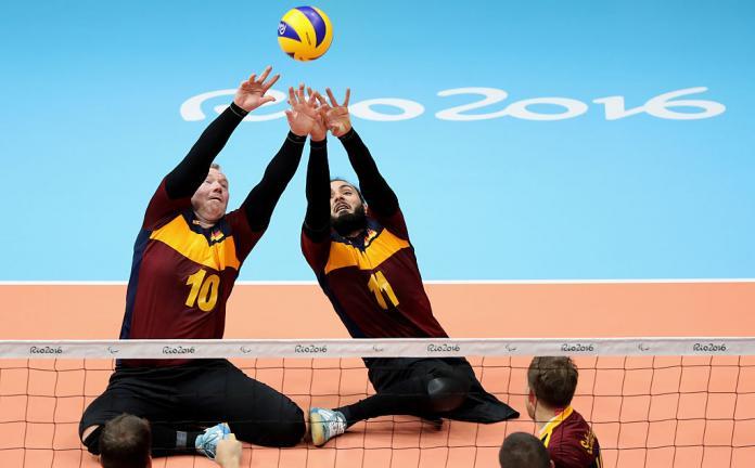 يحاول اثنان من لاعبي الكرة الطائرة الجالسين ضرب الكرة في الهواء