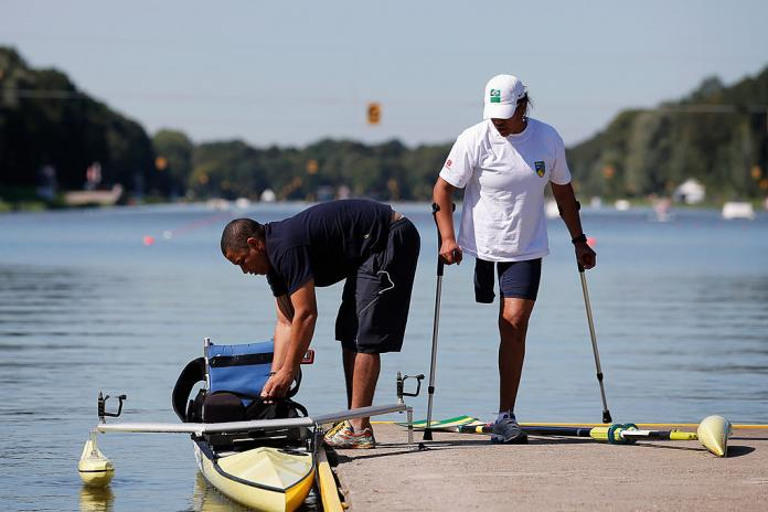 Woman with one leg and crutches amputated waits for her assistant to set up her rowing boat