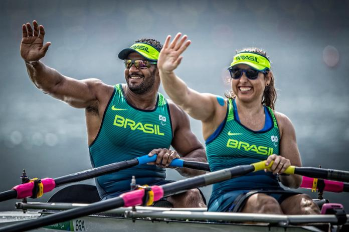 Brazilian male and female rowers smile and wave to the crowd