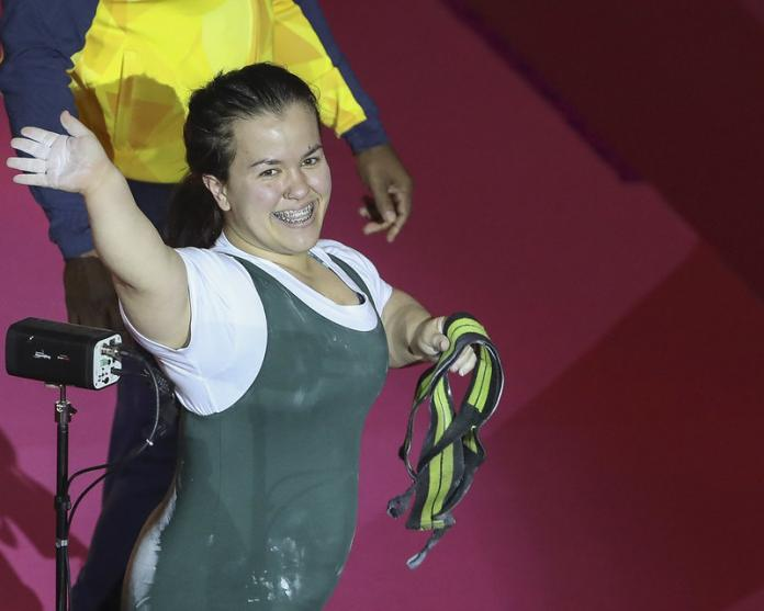 Brazilian powerlifting woman smiles as she waves to the crowd after a lift