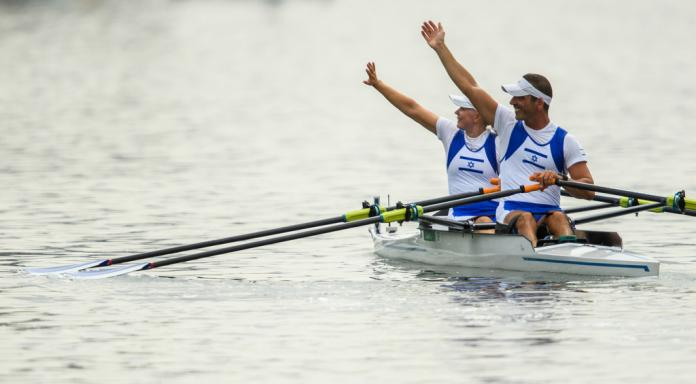 Male and female Israeli rowers wave to the crowd