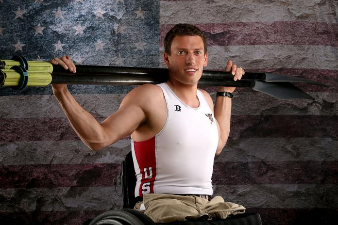 Man poses for portrait with oars on shoulders