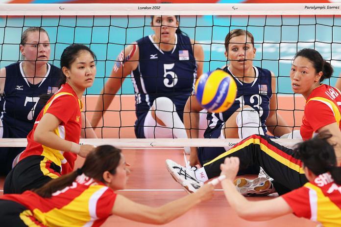 نساء صينيات يجلسن على لاعبي الكرة الطائرة يغوصون لإنقاذ الكرة بينما يشاهد الرياضيون الأمريكيون