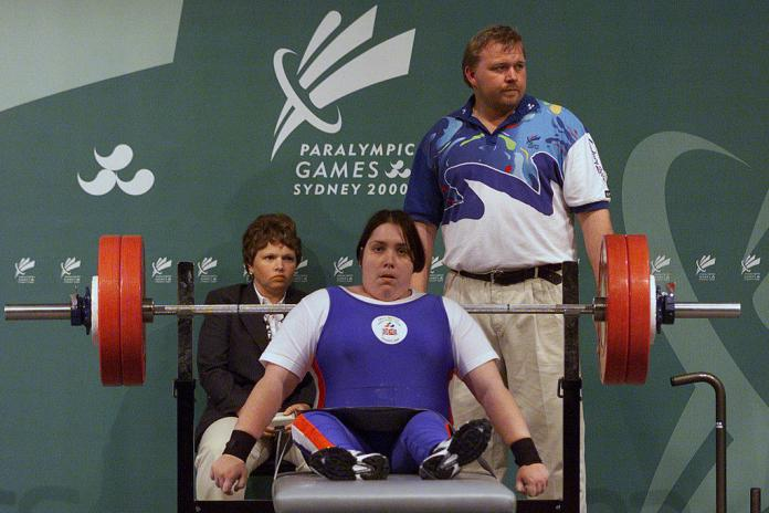 Female powerlifter gets up from her bench