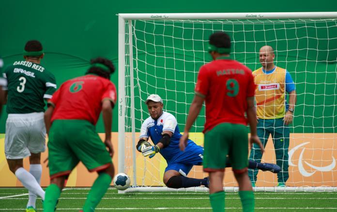 O goleiro tenta bloquear um chute no futsal