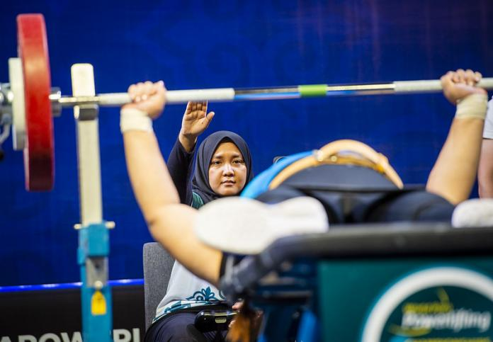 The woman referee behind a powerlifter signals a good lift