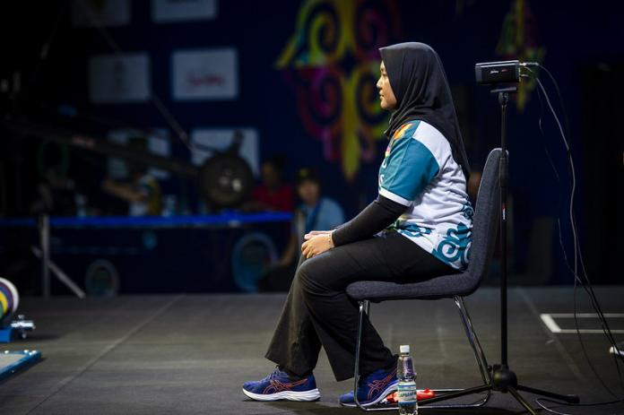 Female powerlifting judge sits and watches
