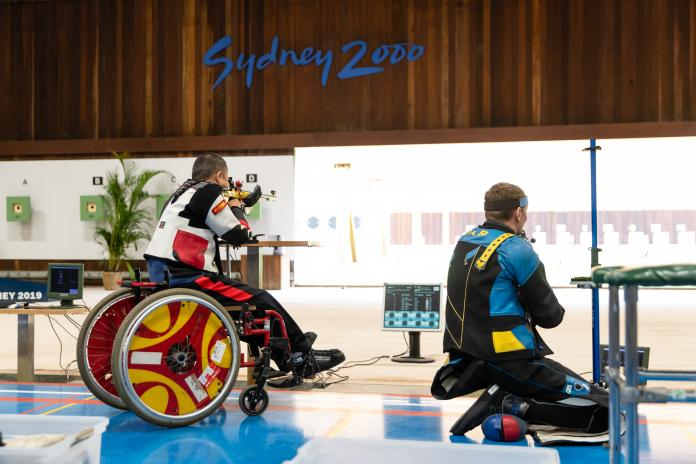 Man kneels to shoot next to another man in wheelchair in Para sport shooting