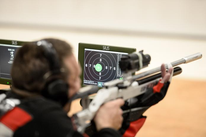 Electronic shooting target next to rifle athlete