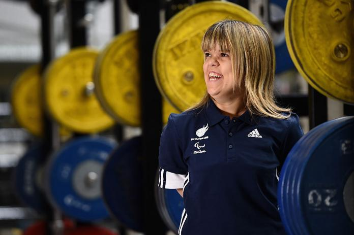 Women powerlifting smiling sideways during a photoshoot