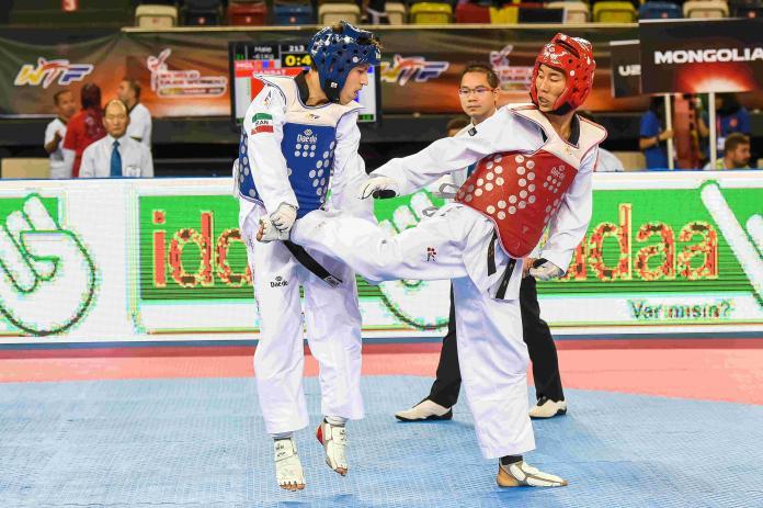 A man kicks his opponent in taekwondo