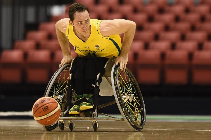 Tom O'Neill-Thorne walks with his wheelchair and the basketball in front of him