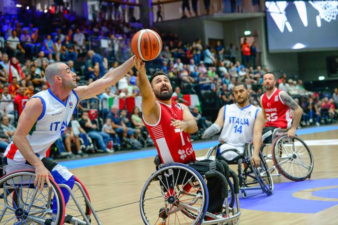 Turkish wheelchair basketball player Ismail Ar shoots as Italian defender tries to block him