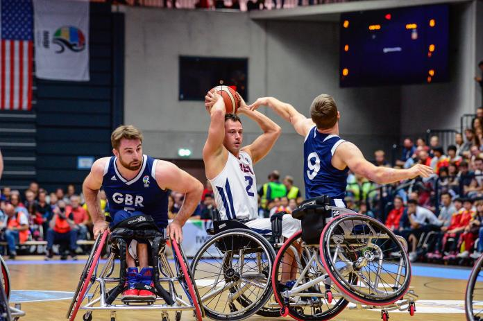US wheelchair basketball player Jake Williams holds the ball over his head, preventing UK defenders from gaining possession