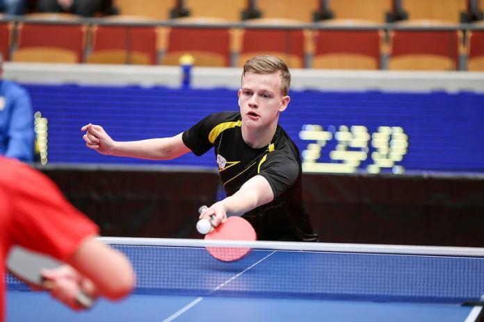 Male table tennis player hits a return shot