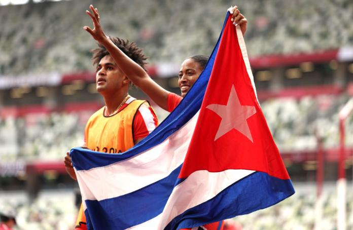 A male and female sprinter holding the flag of Cuba at an athletics stadium