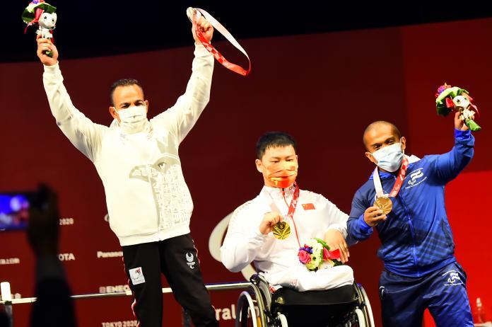 Trīs vīrieši uz skatuves demonstrē savas medaļas