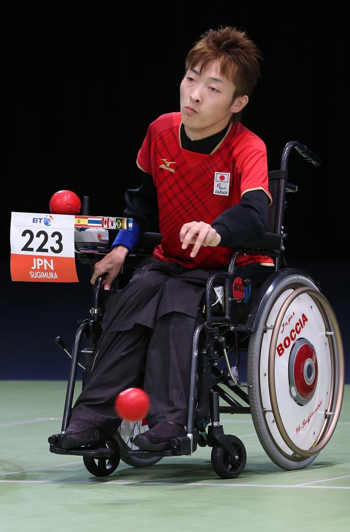Ένας άντρας σε αναπηρική καρέκλα ρίχνει μια κόκκινη μπάλα boccia