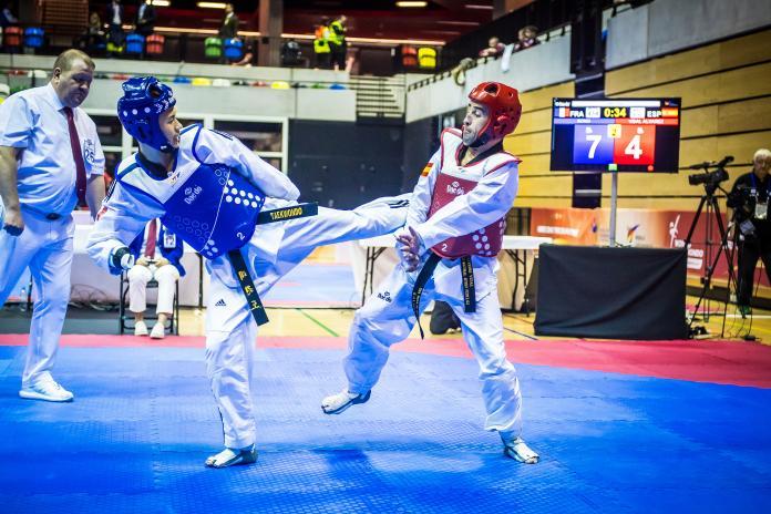 Dos atletas masculinos de taekwondo luchan