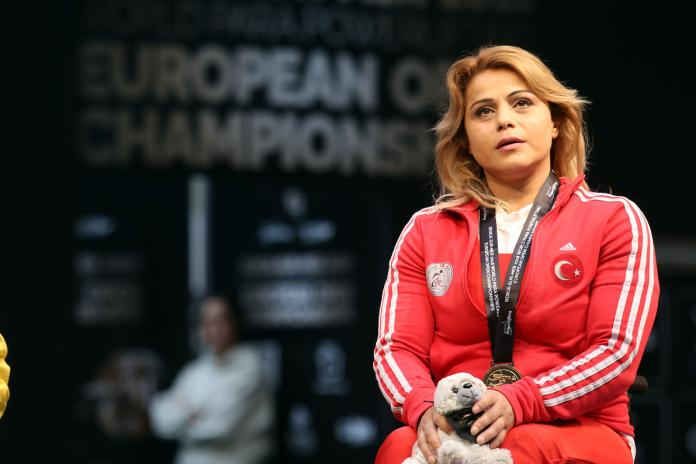 a female powerlifter with her gold medal on the podium